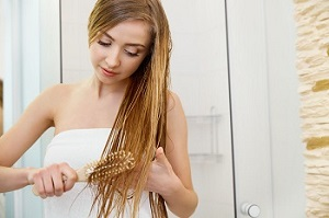 Девушка расчесывает волосы щеткой