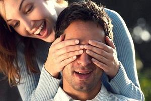 Девушка закрывает глаза мужчине своими руками