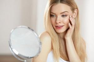 Блондинка смотрит на себя в зеркало