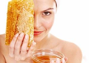 Женщина прикладывает соты меда к лицу