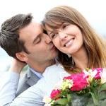 Мужчина целует женщину с цветами в щеку