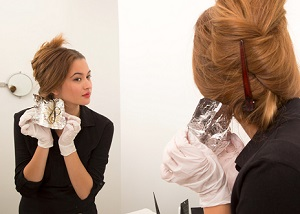 Девушка красит волосы у зеркала